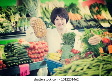Middle aged woman with basket choosing fruits and vegetables on the market