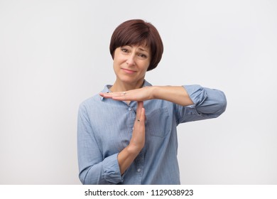Middle aged woman in blue shirt tired and bored, making a timeout gesture, needs to stop because of work stress, time concept
