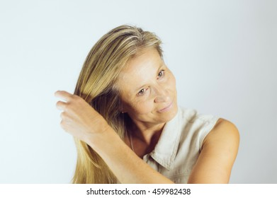 Middle aged woman brushing her hair with a hairbrush.