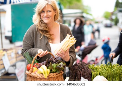 A middle aged woman is buying asparagus and other fresh foods at a farmers market