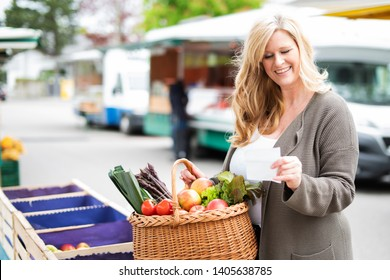 A middle aged woman buys fruits and vegetables at a weekly market and checks her grocery list