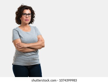 Middle aged woman crossing his arms, serious and imposing, feeling confident and showing power