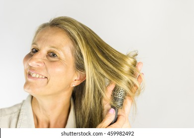 Middle aged woman with dark blonde hair brushing.