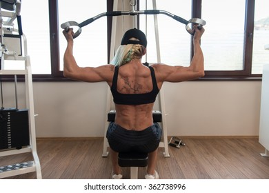 Middle Aged Woman Doing Heavy Weight Exercise For Back In Fitness Centar