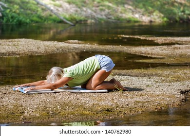 Middle aged woman doing yoga exercises in a natural environment