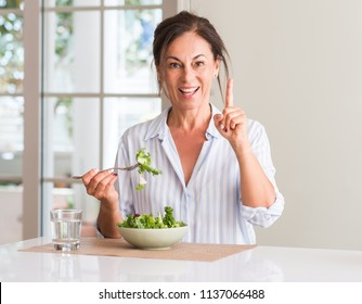 Middle aged woman eating fresh salad in a bowl at home surprised with an idea or question pointing finger with happy face, number one
