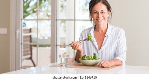 Middle aged woman eating fresh salad in a bowl at home with a happy face standing and smiling with a confident smile showing teeth