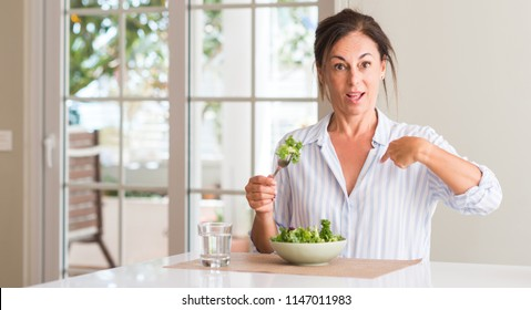 Middle aged woman eating fresh salad in a bowl at home with surprise face pointing finger to himself