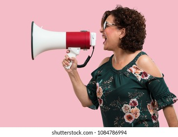 Middle aged woman excited and euphoric, shouting with a megaphone, sign of revolution and change, encouraging other people to move, leader personality