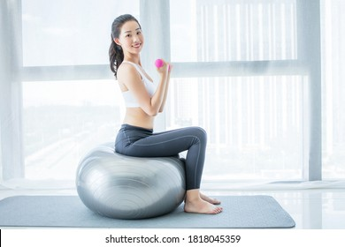 Middle aged woman exercising with dumbbells isolated on white background