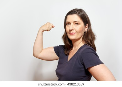 Middle aged woman flexing her biceps muscles, showing self-confidence and pride, white background