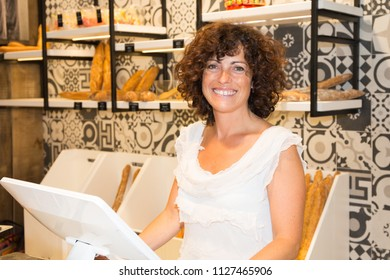 Middle aged woman french baker with tasty bread products in counter bakery