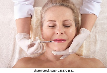 Middle aged woman gets cosmetic injection in her lips. Hyaluronic acid injection for facial rejuvenation procedure. Women in beauty salon. Plastic surgery clinic.