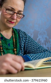 middle aged woman with glasses  reading a book