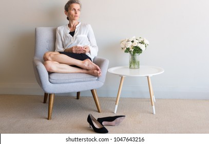 Middle aged woman with grey hair seated in chair holding cup with high heel shoes kicked off on of floor against neutral wall background