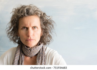 Middle aged woman with grey hair frowning and looking angry against blue background with copy space (selective focus)