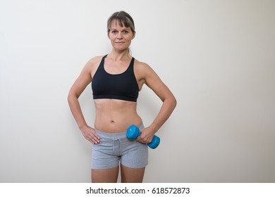 Middle aged woman in gym gear with a blue dumb bell.