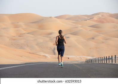 Middle aged woman in gym gear exercising in the desert. Liwa desert, UAE.