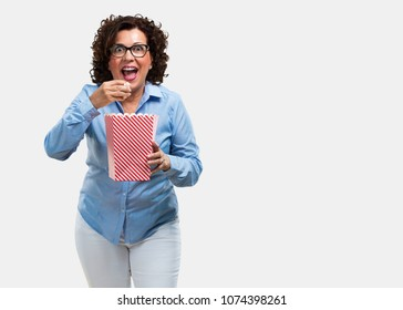 Middle aged woman happy and fascinated, holding a striped popcorn bucket, surprised by the new movie, eyes open and expression of admiration