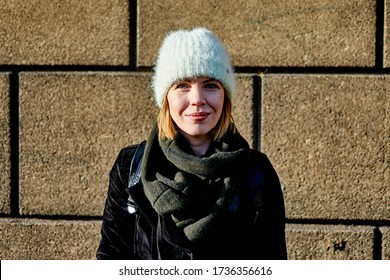 Middle aged woman in hat and coat smiling