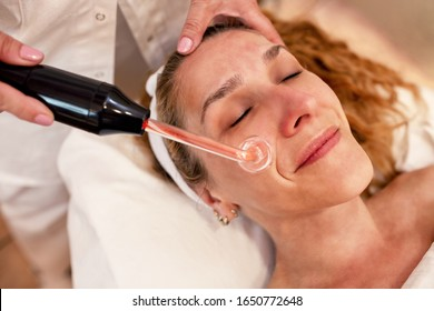 Middle aged woman having a high frequency facial cosmetic treatment, skin treatment concept