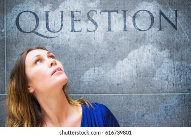 Middle aged woman having questions. Female model looking up, the word question is written on a grey wall.