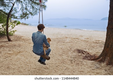 Middle aged woman with her beige dachshund dog sitting on a seesaw on deserted sand beach and looking at sea. Misty day. Seascape with mountains in horizon.