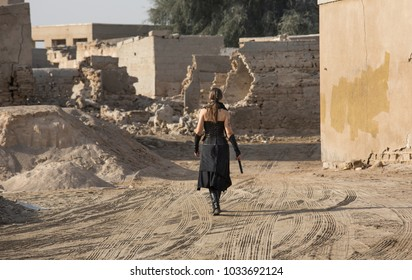 Middle Aged Woman in her fighting outfit  walking around her destroyed village looking around for ennemies