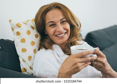 middle aged woman holding cup of coffee at her home