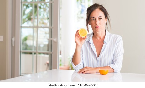 Middle aged woman holding orange fruit with a confident expression on smart face thinking serious