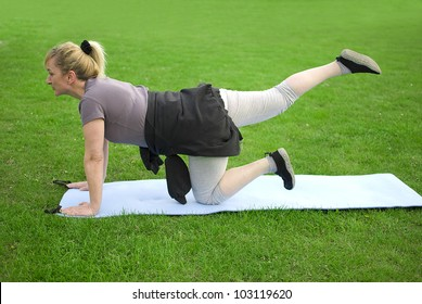 middle aged woman keeping fit with exercises in a park