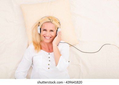 A middle aged woman listening with headphones to music in bed.