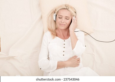 A middle aged woman listening to music with headphones in bed.