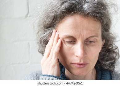 Middle aged woman looking sad and tired and rubbing temple (selective focus)