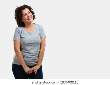 Middle aged woman looking up, thinking of something fun and having an idea, concept of imagination, happy and excited