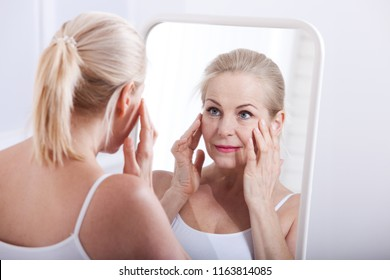 Middle aged woman looking at wrinkles in mirror. Plastic surgery and collagen injections. Makeup. Macro face. Selective focus on the face. Realistic images with their own imperfections.
