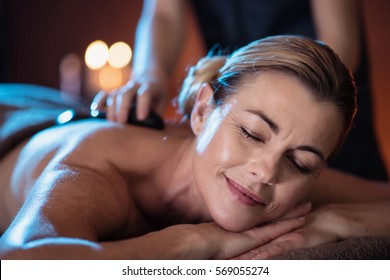 a middle aged woman lying on a massage table in a beauty salon with hot stones on her back