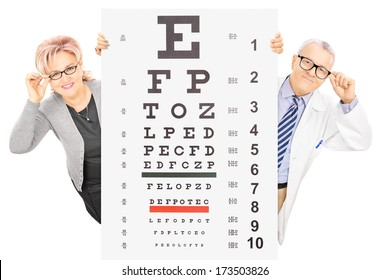 Middle aged woman and a male optician standing behind eyesight test isolated on white background