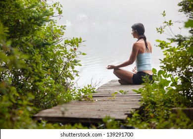 middle aged woman meditating on dock by a lake in the foggy morning, horizontal composition, Surry Maine