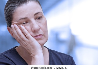 Middle aged woman nearly falling asleep in the office. Tiredness because of sleep apnea syndrome, insomnia, winterblues or fibromyalgia