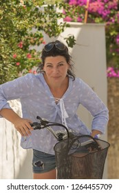 Middle aged woman on top of a retro bicycle at Andros island in Greece.