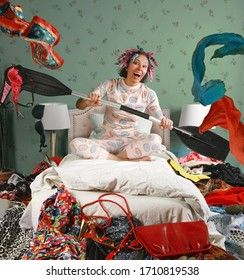 Middle aged woman in pajamas and curlers is sitting on a bed paddling as if in a boat through a pile of scattered clothing in complete disarray. The theme of excessive consumption of things