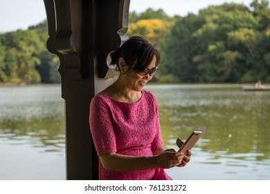Middle aged woman in a park, checking her smarphone with happy smile