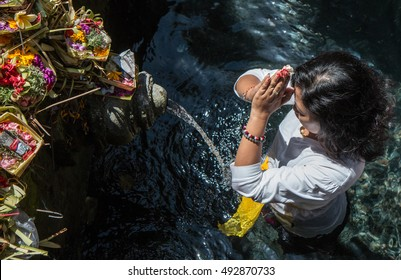 Middle aged woman performing a ritualistic prayer in the Tirta Empul water temple in Bali, Indonesia. 12/SEP/2016