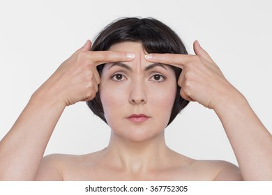 Middle aged woman point at worry wrinkles, concept of anti-age therapy, botox