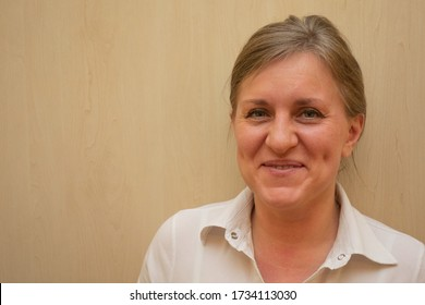 Middle aged woman portrait. Caucasian 40 years woman looking at camera and smiling. White business shirt is dressed. Happy face and positive emotions. Background with copy space