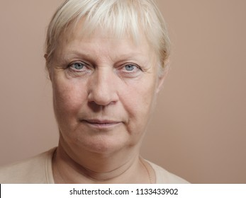 Middle aged woman portrait on light background.