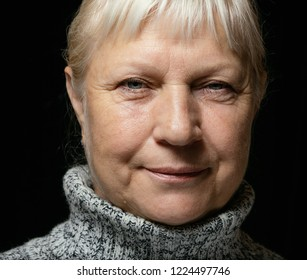 Middle aged woman portrait in sweater on dark background.