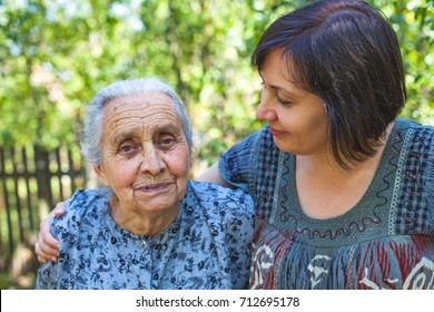 Middle aged woman posing with her sick old mother in the garden