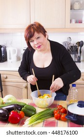 Middle aged woman posing with vegetable salad in kitchen